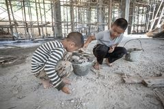 Poor children working at construction site against children labour, World Day Against Child Labour and trafficking concept. stock photography