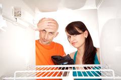 Poor couple looking in fridge. Poor couple with empty wallet looking in bare interior of empty modern refrigerator stock image