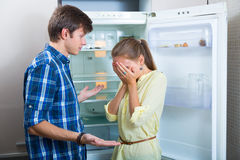 Poor couple near empty fridge Stock Photography