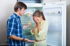 Poor couple near empty fridge Stock Photography