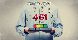Poor credit score theme with man holding a tablet. Poor credit score theme with young man holding a tablet computer stock photography