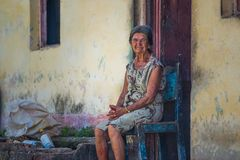 Poor Cuban people Old woman sitting in street of Caribbean communism village, Havana, Cuba, America. An Old senior Cuban people lady with a chair and hat in royalty free stock photography