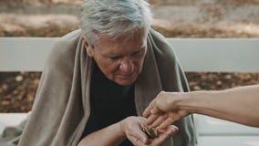 Poor elderly homeless man receiving coins from the passenger