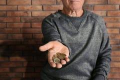 Poor elderly man begging for money near brick wall. Focus on hand royalty free stock photos
