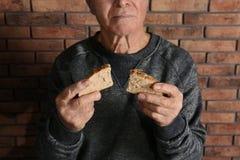 Poor elderly man with bread near brick wall. Closeup royalty free stock photography