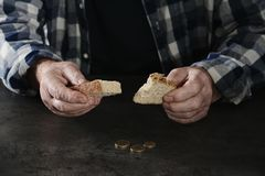 Poor elderly man with bread at table, focus. On hands stock photo