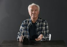 Poor elderly man with empty wallet and coins at table. On dark background royalty free stock photo