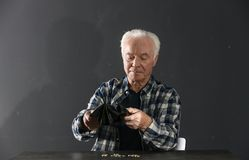 Poor elderly man with empty wallet and coins at table. On dark background stock photo