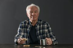Poor elderly man with piece of bread and metal mu. G at table against dark background royalty free stock images