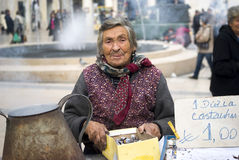 Poor elderly woman sells chestnuts. On the street of Coimbra, Portugal Royalty Free Stock Photo