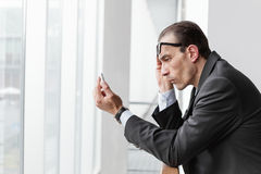 Poor eyesight man trying to watch his phone display Stock Photo