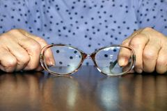Poor eyesight in old age. Horizontally.Hands of an elderly woman sitting at a table, holding glasses in hands Royalty Free Stock Photo