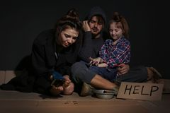 Poor family with HELP sign and coins on floor. Near dark wall stock photo