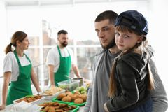 Poor father and daughter receiving food from volunteers. Indoors royalty free stock photos
