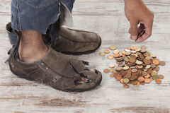 Poor feet. Concept of a poor person and his feet with some coins royalty free stock photos