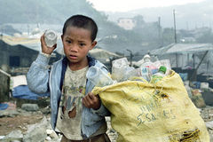Poor Filipino boy gathering plastic on landfill stock photos