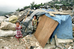 Poor Filipino children live, work on garbage dump. Philippines, island Luzon, Baguio City: children, boy and girl, standing in front of their hut, home. These stock photography