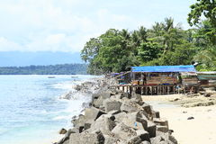 Poor fishers house. Made from wood on pillars on beach in Manokwari, Papua Barat, Indonesia Royalty Free Stock Image