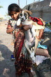 Poor Girl with Dog. A poor beggar girl from India posing with her street dog, on the street-side stock image