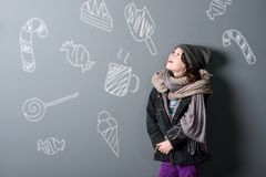 Poor girl dreaming about sweets. Poor little girl with a happy smile, close-up. Shabby clothes, sweet treats on the grey background. Dreaming about tasty food stock image