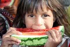 Poor Girl Eating Melon. A poor & hungry girl from India eating a ripe watermelon Royalty Free Stock Photo