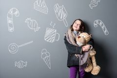 Poor girl holding old toy. Poor girl holding an old toy looking upwards, close-up. Shabby clothes, chalk drawings of sweets on the grey background. Help poor royalty free stock photos