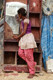 A poor girl looking in a mirror from a urban slum in new delhi. A poor girl in natural habitat looking in a mirror in a slum from new delhi, india royalty free stock photo