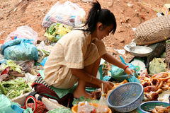 Poor girl selling food. Poor cambodian girl selling food on the market in Phnom Penh Royalty Free Stock Photo