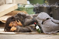 Poor girl tramp. Poor woman tramp lying among bin with wine bottle Royalty Free Stock Photos