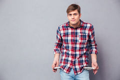 Poor handsome young man in checkered shirt showing empty pockets. Poor handsome young man in checkered shirt and jeans showing empty pockets over grey background Stock Photo