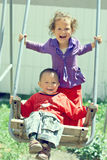 Poor but happy little gypsy siblings on swing Royalty Free Stock Photo