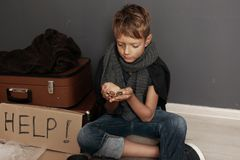 Poor homeless boy begging on floor. Near dark wall royalty free stock photo