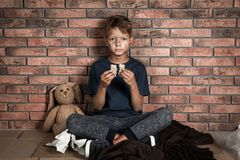 Poor homeless boy holding bread in hands. Near brick wall royalty free stock images
