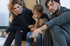 Poor homeless family begging. On city street royalty free stock photos