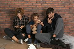 Poor homeless family sitting on floor. Near brick wall royalty free stock photo