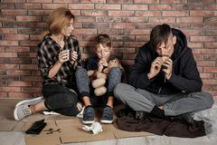 Poor homeless family sitting on floor. Near brick wall royalty free stock images