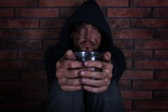 Poor homeless man begging near wall. Poor homeless man begging near brick wall stock photography