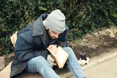 Poor homeless man with book on street. In city royalty free stock image