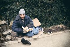 Poor homeless man with book on street. In city stock images