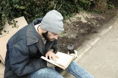 Poor homeless man with book on street i. N city stock photos
