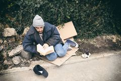 Poor homeless man with book on street. In city stock photo