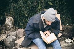 Poor homeless man with book on street. In city royalty free stock images