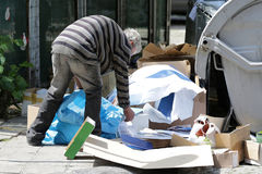 Poor homeless man collecting paper. Poor homeless man collects paper near trash bins for recycling in Sofia, Bulgaria. A decade after joining the EU many people royalty free stock photo