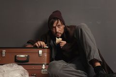Poor homeless man eating. Near dark wall stock image