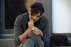 Poor homeless man eating piece of bread. On city street royalty free stock photo