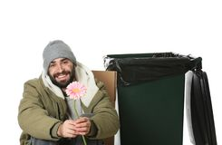 Poor homeless man with flower near trash bin isolated. On white stock photo