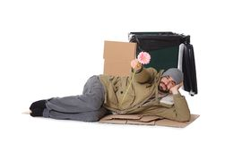 Poor homeless man with flower near trash bin isolated. On white royalty free stock images