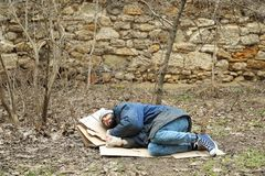 Poor homeless man lying on ground in park. Poor homeless man lying on ground in city park royalty free stock image