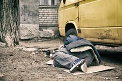 Poor homeless man lying near van. Outdoors royalty free stock images