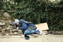 Poor homeless man lying on street. In city stock photo